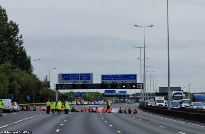 Insulate Britain protesters sit on the M25 yesterday near junction 14 for London Heathrow Airport - this group, who could have been killed when they walked into the road, took four hours to arrest and remove