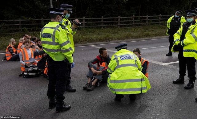 Police officers speak to a protester who stopped traffic at junction three of the M25 at Swanley in Kent this morning
