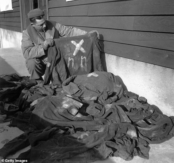 An American soldier examines the clothing of prisoners outside one of the factory workshops at the concentration camp