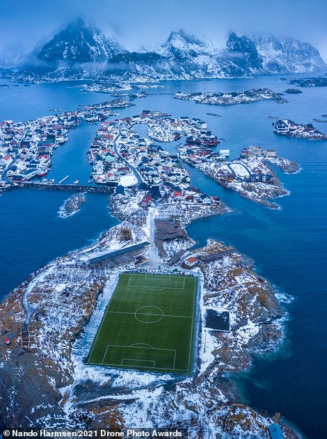 This photograph is deemed highly commended in the Urban category by the judges. Nando Harmsen directed his drone into the air over Henningsvaer in the Lofoten archipelago, Norway, in a bid to capture the picture. 'The football field of the fishing town called Henningsvaer is a special one,' the photographer says. 'The green artificial grass stands out from the winter landscape'