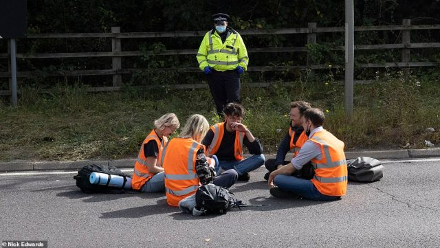 A police officer watches over protestors at junction 3 of the M25 this morning amid scenes of traffic chaos