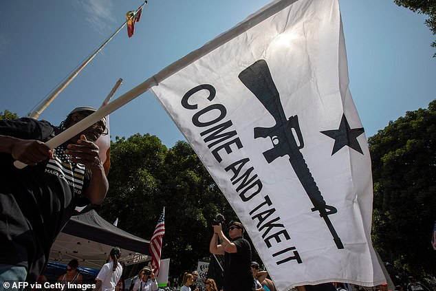 The phrase 'Come and Take It' has also been invoked by gun rights advocates. The image above shows a man waving a flag with the words 'Come and Take It' written on it during a protest in Los Angeles on August 14