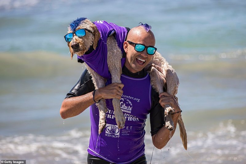 Kioni Russell Gallahue and his surfing partner Derby exit the water after competing at the 16th Annual Surf Dog Surf-A-Thon
