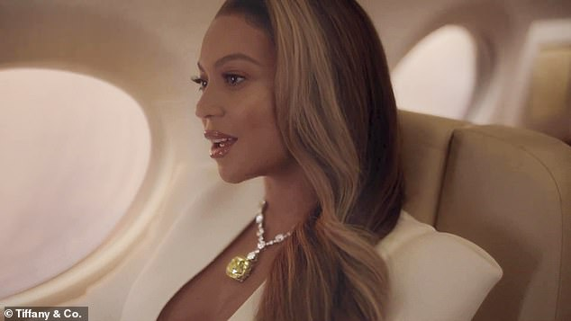 Love on Top: Beyonce sat by the window on a private jet and wore a stunning white suit to complement the brilliant yellow bauble on her neck as she waited to be reunited with her love