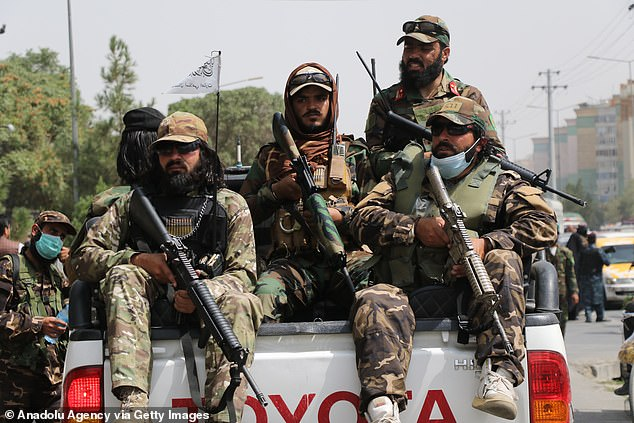 Aria recalled being slammed in the back and shoulders withTaliban soldiers' guns. Pictured: Taliban fighters patrolling the streets on Saturday, September 11