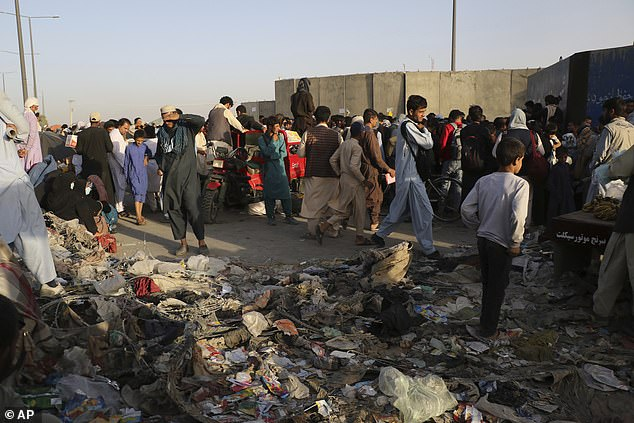 Hundreds of people gather near an evacuation control checkpoint during ongoing evacuations at Hamid Karzai International Airport, in Kabul Wednesday, August 25