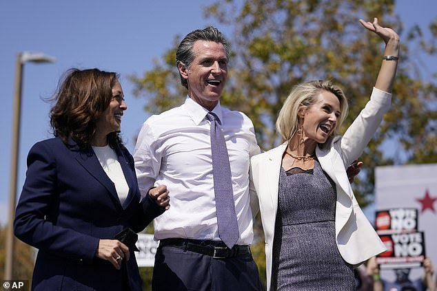 Vice President Kamala Harris (left) stands on stage with California Governor Gavin Newsom (center) and his wife Jennifer Siebel Newsom (right)