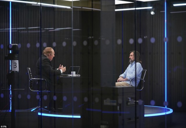 Presenters Andrew Neil and Neil Oliver broadcast from a studio during the launch event for GB News