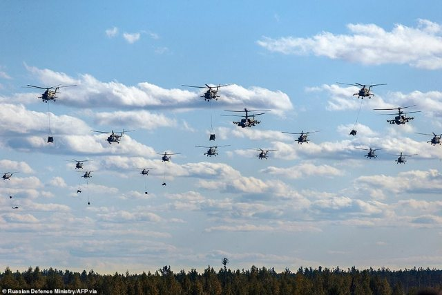 Helicppters fly in formation during military exercises on Monday