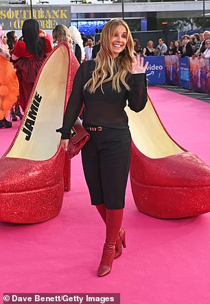 Red carpet: Louise donned a pair of knee-high red boots while she carried a matching bag