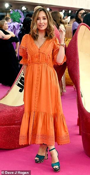 Looking good: Myleene Klass showcased her sense of style in a bright orange midi dress with a pleated hemline
