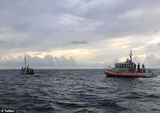 U.S. Coast Guard approaches a vessel (left) with 104 Haitian migrants after the boat was spotted18 miles off the coast of Miami
