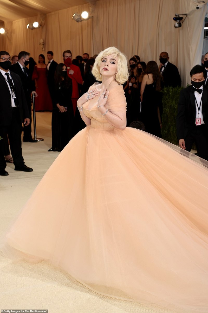 Strike a pose:The 19-year-old Grammy Award-winner wowed in a billowing peach ballgown with a lengthy train that trailed behind her as she posed for shutterbugs