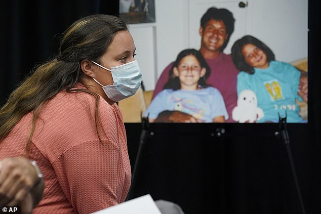 Rachel Howell, daughter of murder victim Paul Howell, sits next to a large photo of her father as she listens during a commutation hearing before the Oklahoma Pardon and Parole Board for his convicted killer, Julius Jones
