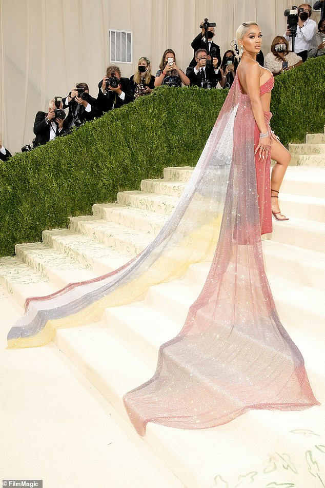 All eyes on her: She showed off the sheer multi-colored train as she walked up the steps to the museum