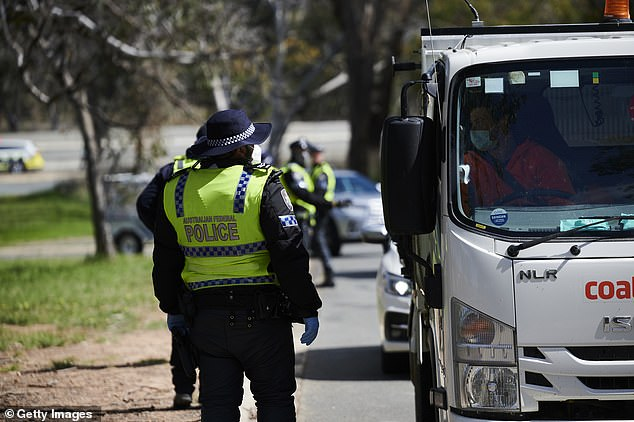 Police check cars on the New South Wales-ACT border after the territory extended its current lockdown by a further four weeks on Tuesday