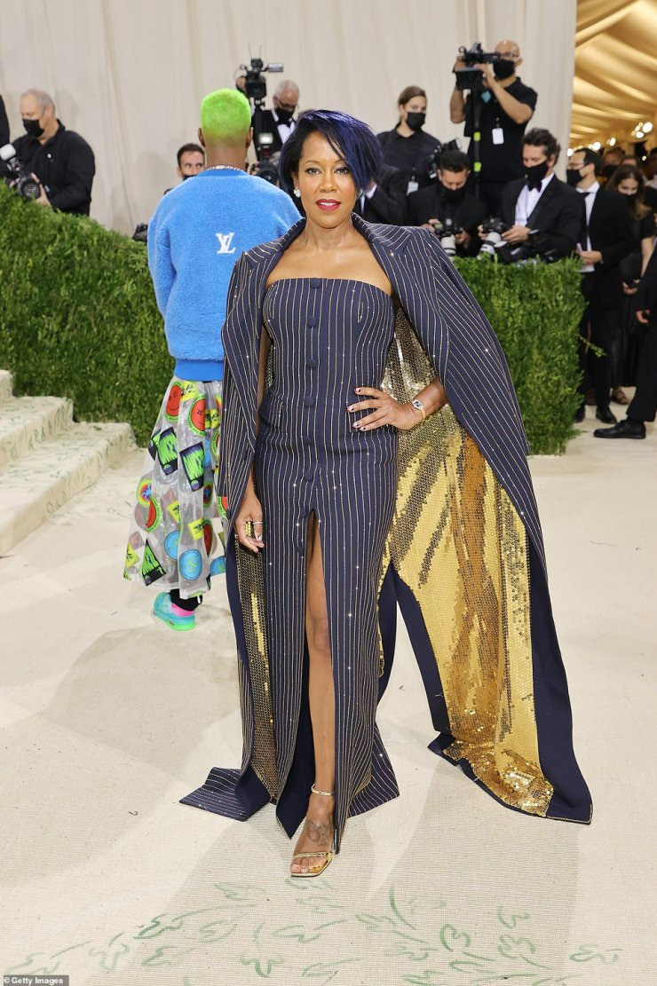 Sleek: Regina King donned a navy pinstripe dress with gold sequins woven under the cape detail; she is wearing Michael Kors