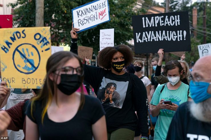 Signs from protestors marching outside his home call on Kavanaugh to resign or be impeached