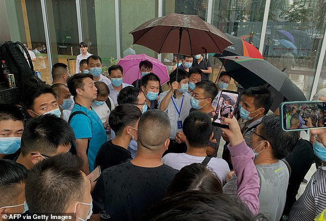 Protesters mob the headquarters of property giant Evergrande in Shenzhen, southeastern China, to demand their money back after it was revealed the company owes $300billion