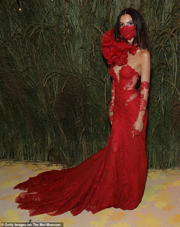 Safety first:Emily showed off her mask once she was inside the event. It was a lacy red mask that appeared to have been designed in conjunction with her ensemble