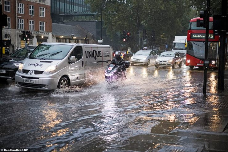 Downpour: Traffic ploughs through surface water on the Euston road in North London during heavy rainfall this morning