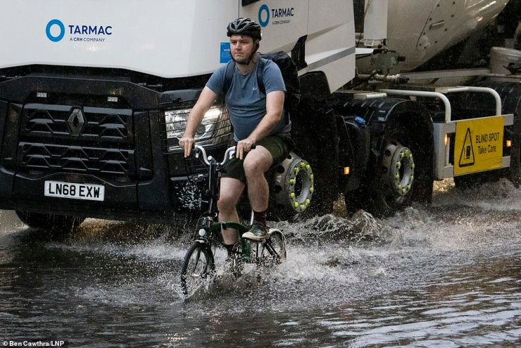 Pictured: A cyclist ploughs through surface water on the Euston road in North London during heavy rainfall