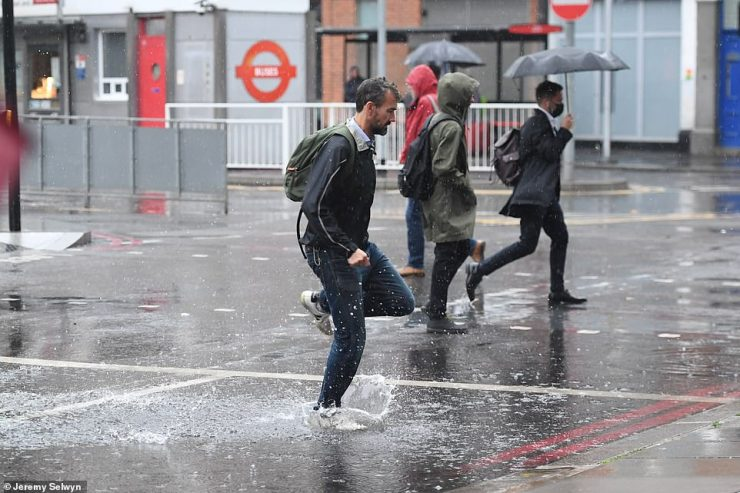 Commuters splash through large puddles near London Victoria station this morning as the capital is battered by rain