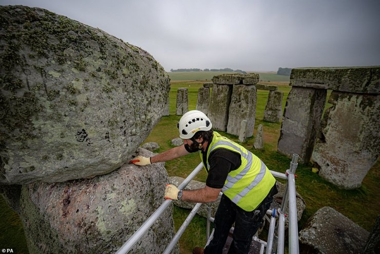 Conservator James Preston uses a pointing spoon on top of a scaffold erected inside the stone circle at Stonehenge as specialist contractors from SSH Conservation fix defects from previous repairs
