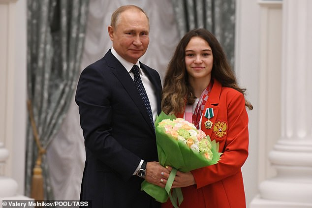 Putinposes with swimmer Viktoria Ishchiulova during a state award ceremony for medallists of the 2020 Summer Paralympic Games yesterday