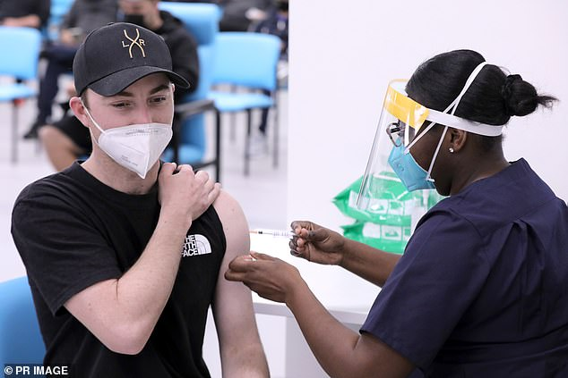 Pictured: A young man rolls up his sleeve to get the Covid vaccine inSydney's Macquarie Fields