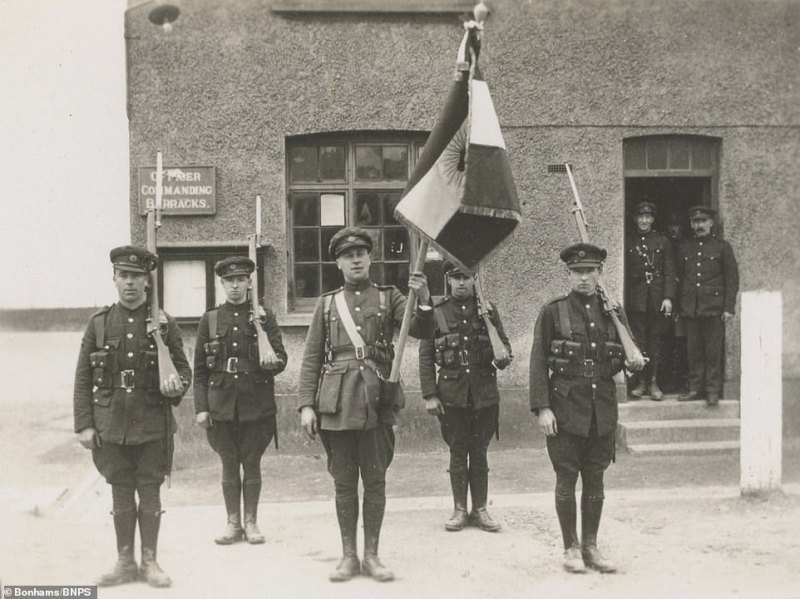 This image of soldiers standing while others watch from a doorway is one of 200 images, mostly taken in 1921 and 1922