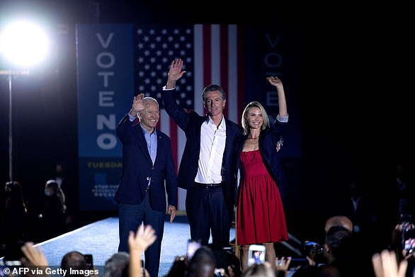 President Joe Biden (left) is joined by California Gov. Gavin Newsom (center) and his wife Jennifer Siebel Newsom (right) onstage at the conclusion of the Long Beach rally