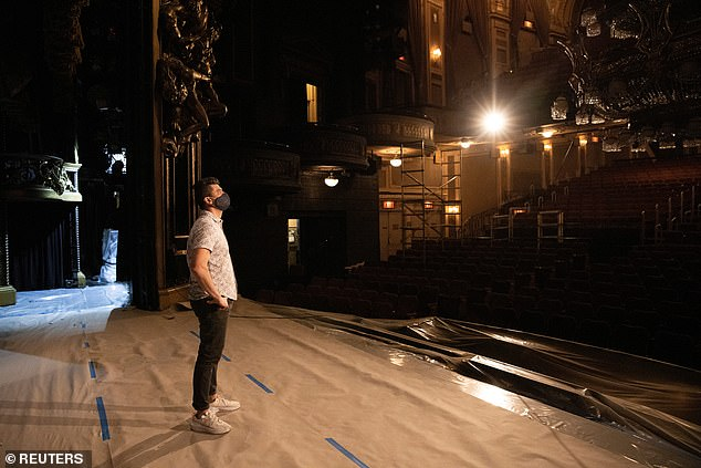 An actor stands in an empty theater with a mask on as performers prepared for reopening. It cost shows between $1.4million and $4million to re-rehearse