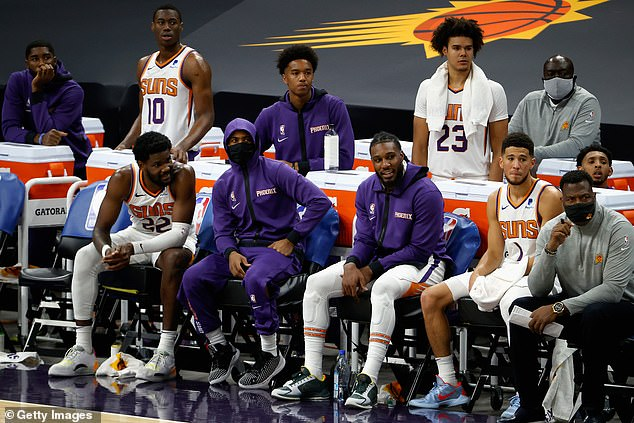 Phoenix Suns center Deandre Ayton (seated far left) chats with NBPA president Chris Paul (center left), who is seen wearing a mask during a December game
