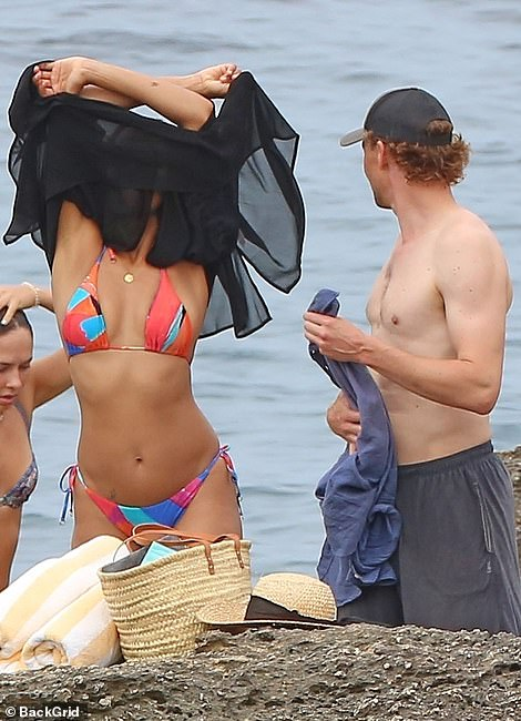 The look of love:The Loki actor, 40, looked lovingly over at his girlfriend, 37, as they stripped off into their swimwear