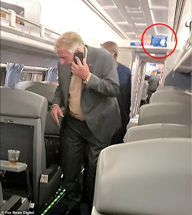 Another photo shows McAuliffe hunched over in the train aisles, still maskless, in front of a sign asking customers to wear masks