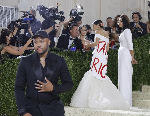 AOC is interviewed on the steps of the Met Gala while designer Aurora James waits by her side and celebrities walk the famed carpeted stairs