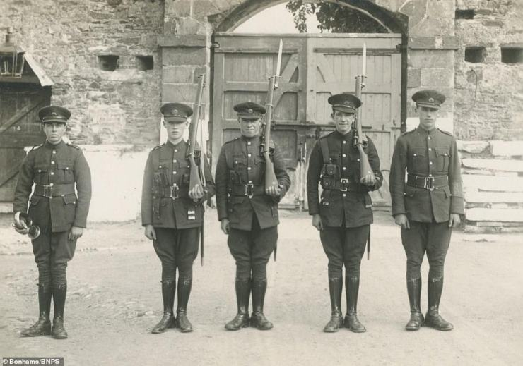 Five soldiers pose proudly in their uniforms for a photo, with three of the men holding their rifles on their shoulders