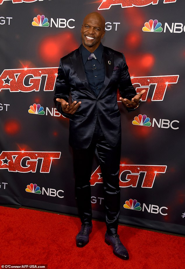 Muscle man:Host Terry Crews highlighted his muscular frame in a satin suit jacket and straight-leg trousers