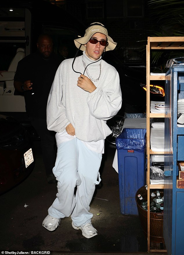 Quirky: Justin, 27, showed off his own signature style in a slouchy white jumper, joggers and a wide floppy hat
