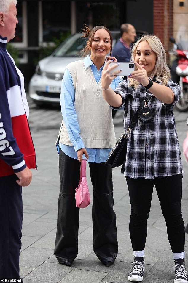 Smile: The musician stopped to take pictures with fans and she strutted to the studios