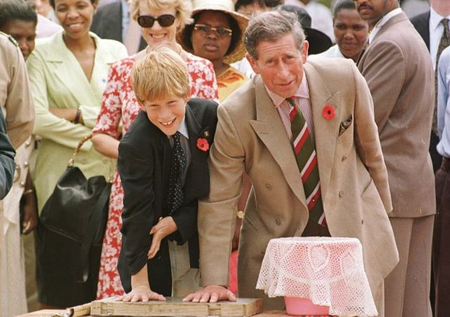 The Prince of Wales is pictured with Prince Harry leaving their mark in cement, at the Dukuduku village school in South Africa in 1997