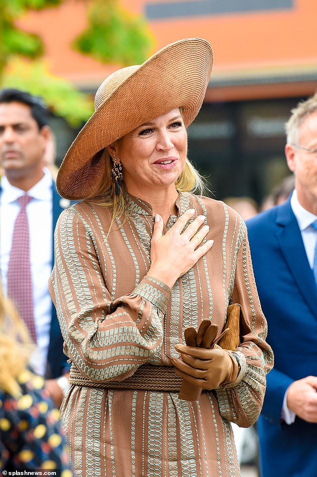 Queen Maxima, 50, sported a brown chiffon dress that showcased detailed teal embroidered stripes which she paired with soft brown leather gloves to compliment