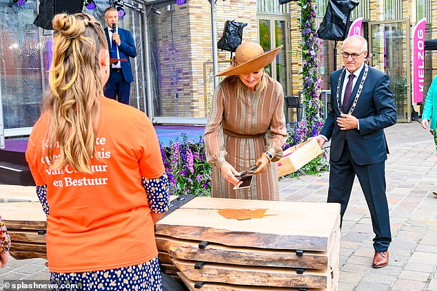 Upon starting her tour, the Dutch Queen inspected some wooden seating and walked around the site while talking to officials