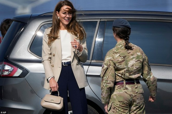 Kate smiles as her hair is blown in the wind as she meets military personnel at RAF Brize Norton in Oxfordshire this morning