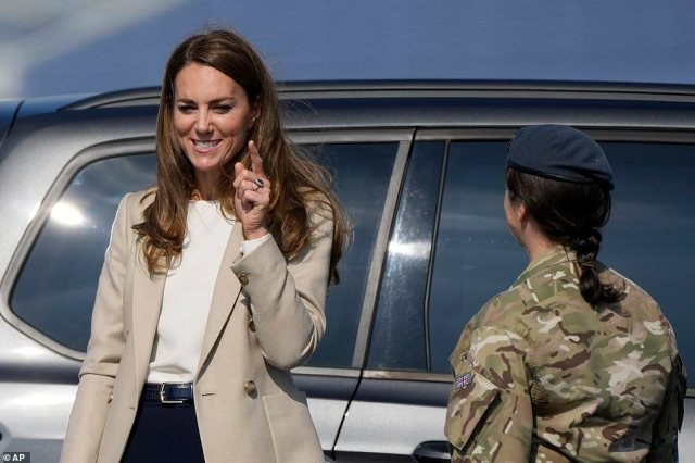 Kate smiles as she meets a member of the armed forces during her visit to RAF Brize Norton in Oxfordshire this afternoon