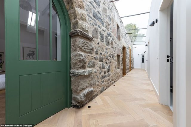 Meanwhile the modern extension was connected to the 150-year-old bothy with a lengthy white corridor and glass ceiling (pictured)