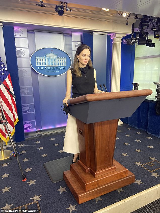 Movie star Angelina Jolie posed for pictures on the White House briefing room podium on Wednesday during a surprise visit.'It feels just like it should feel, feels very serious,' she said