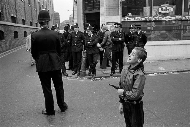 A small boy is seen holding a toy gun in front of a group of police officers on Brick Lane in the 1990s