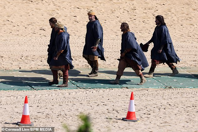 On location: Fouractors in identical outfits were seen walking across the beach